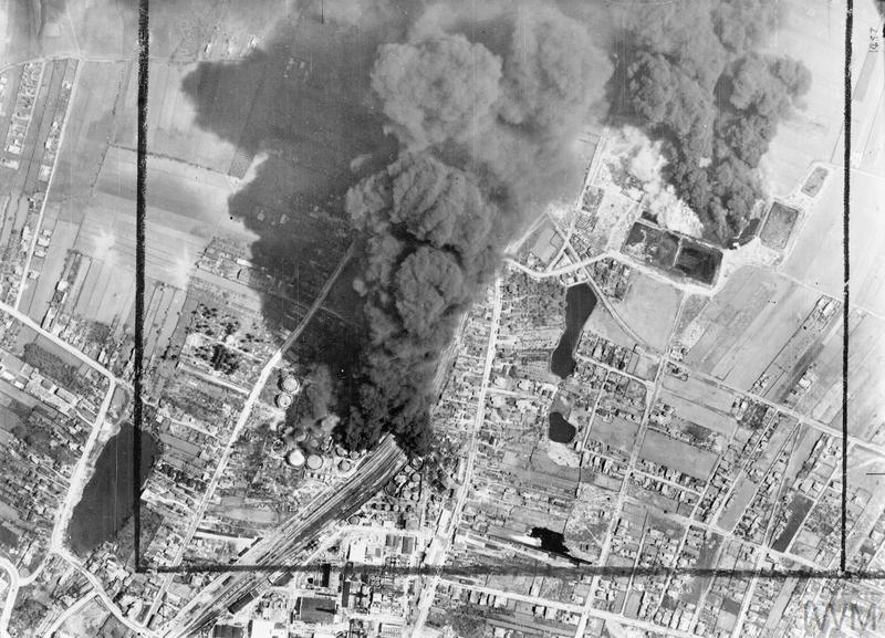 Vertical photographic-reconnaissance aerial taken over the oil refinery and marshalling yards at Campina, 20 miles north-west of Ploesti, Romania, following an early morning attack by Handley Page Halifaxes and Vickers Wellingtons of No. 205 Group RAF. Smoke from burning oil tanks is drifting over the target area, which was also attacked by Consolidated Liberators of the 15th USAAF, half and hour after this photograph was taken. It is not certain, that this was the operation, Høyer participated in on 5/6 May 1944. &copy IWM (C 4346).